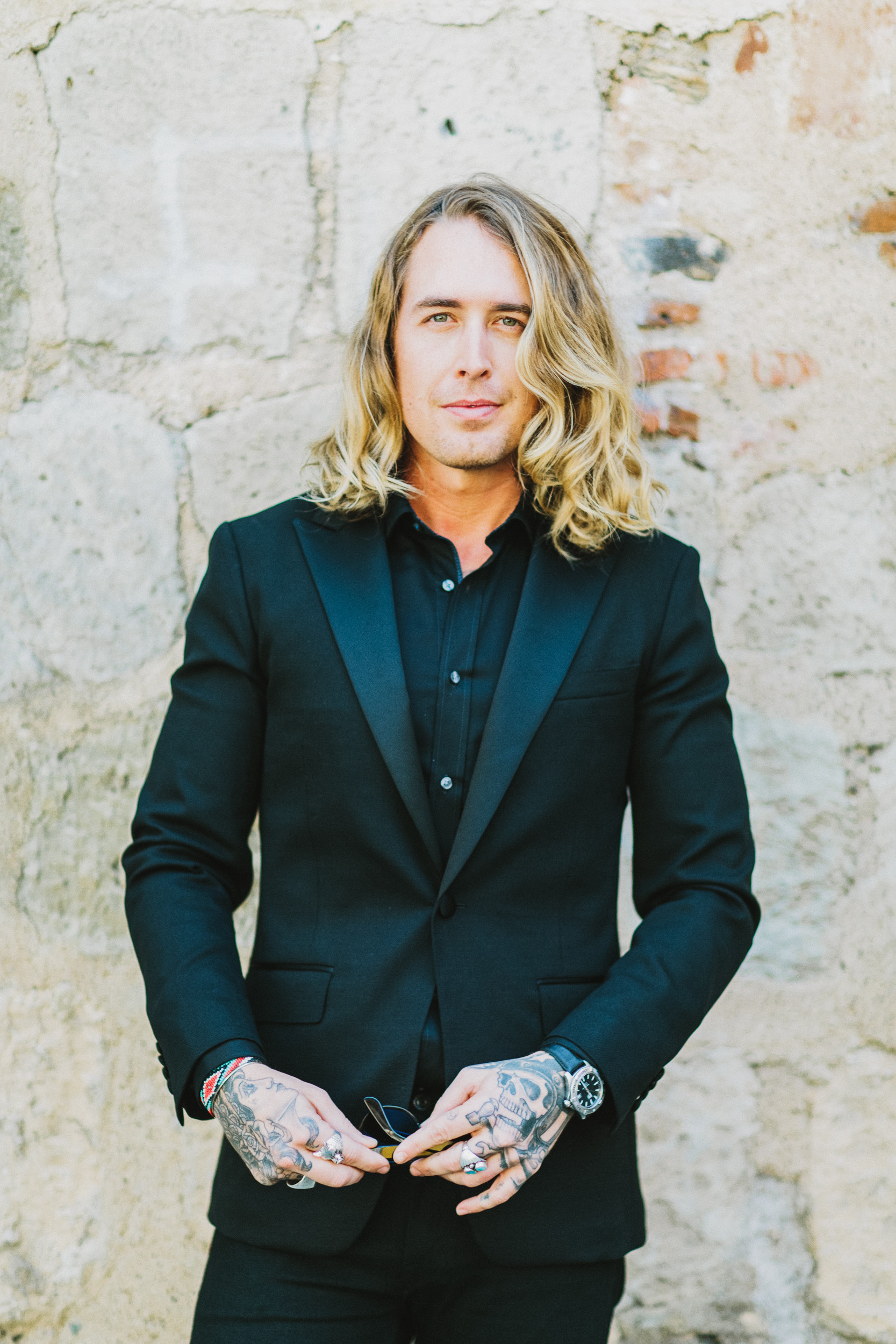 tattooed groom with long blonde hair wearing all black