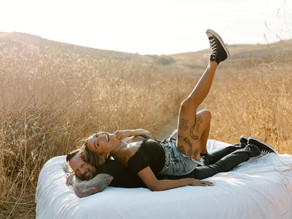fun and flirty engagement session with a mattress in a field