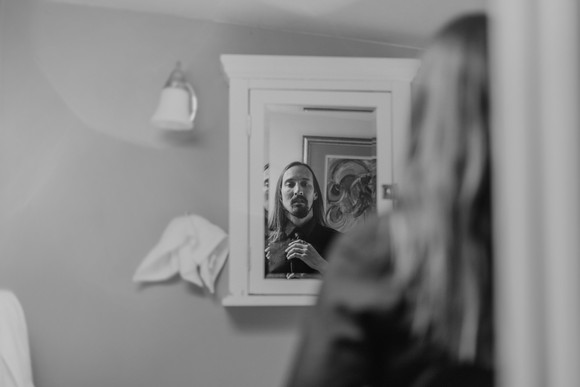 groom with long hair getting ready in mirror
