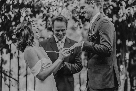bride laughing while putting ring on groom's hand
