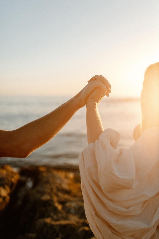close up holding hands at sunset laguna beach