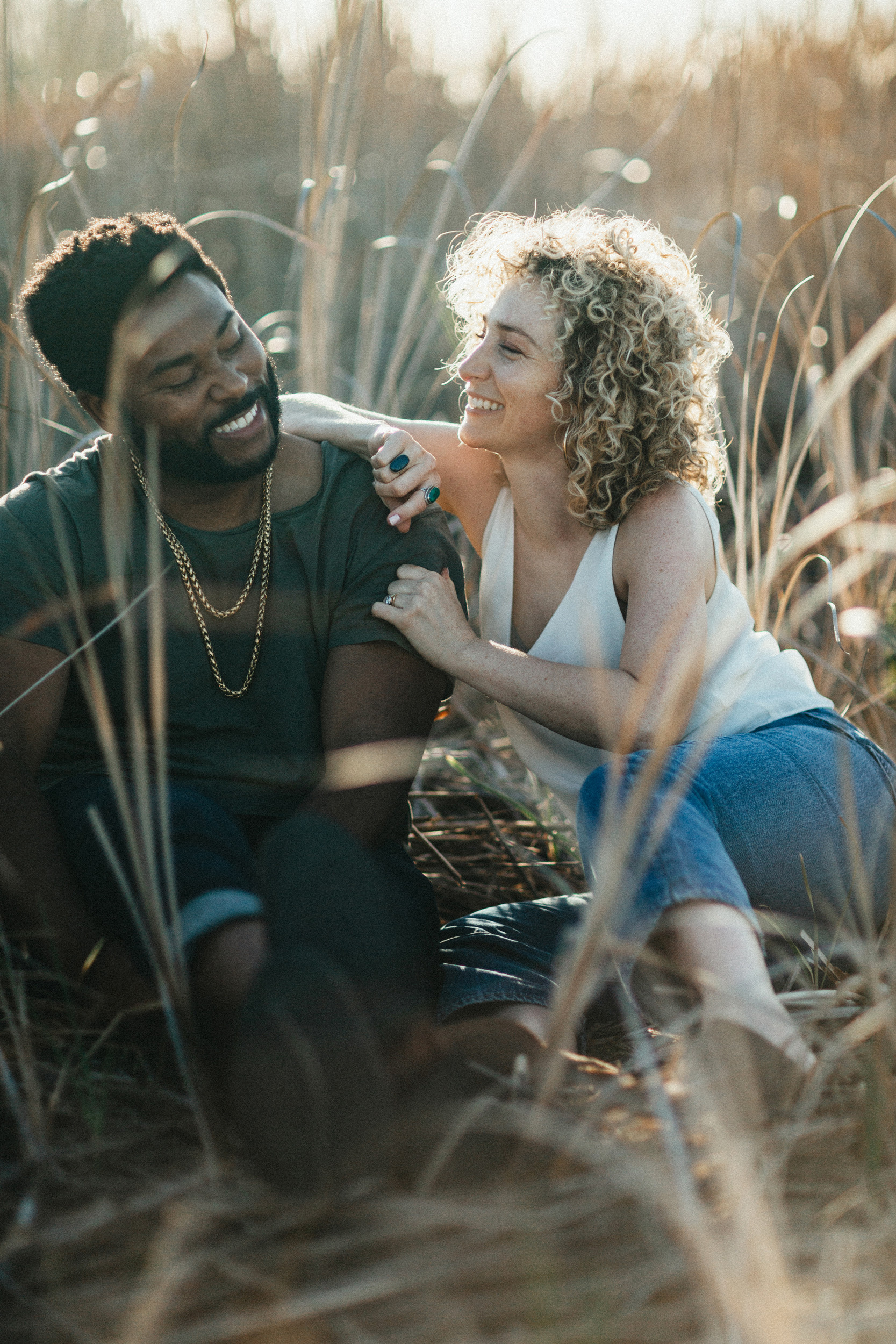 biracial couple laughing in field engagement photos