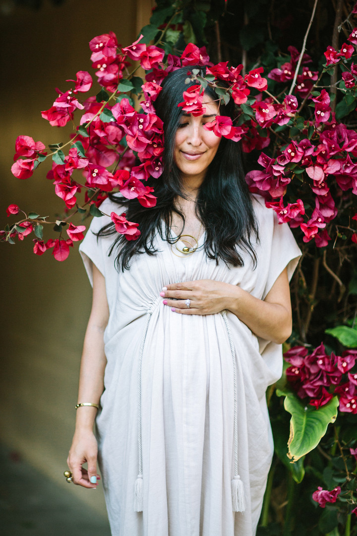 pregnant mother surrounded by flowers maternity session