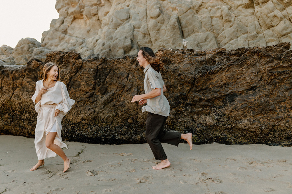 guy chasing girl divers cove laguna beach engagement photos