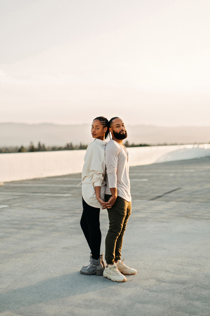 couple standing on top of parking garage at sunset