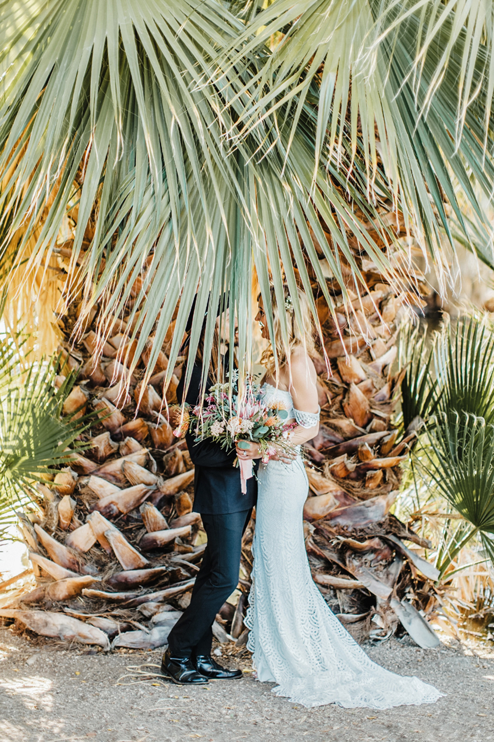 bride and groom behind palm fronds
