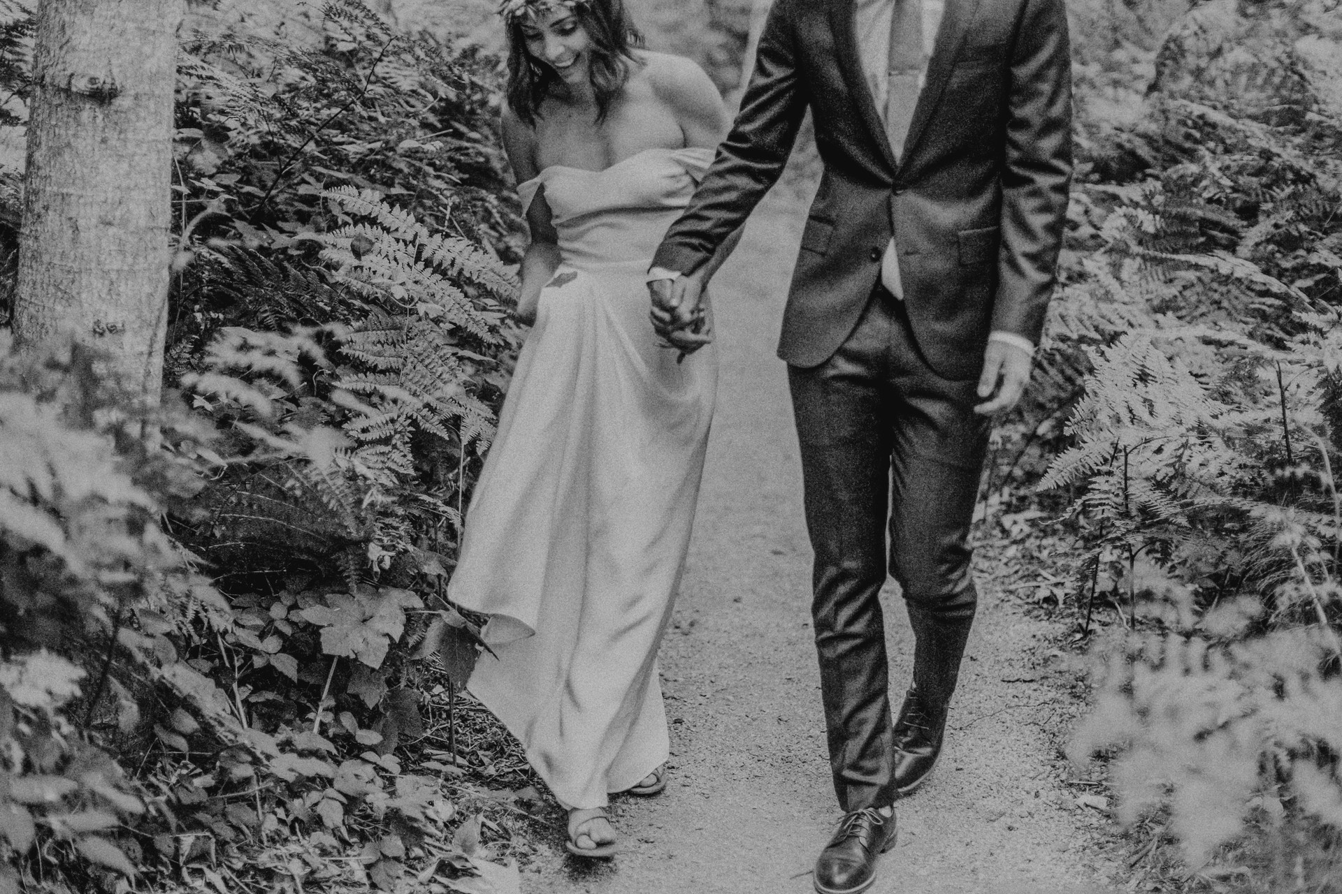 glen oaks big sur bride and groom walking through ferns