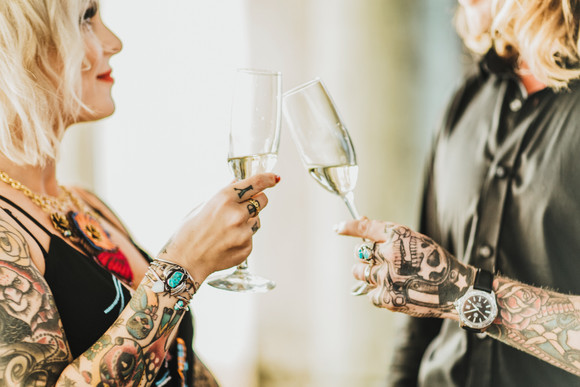 tattooed bride and groom toasting champagne