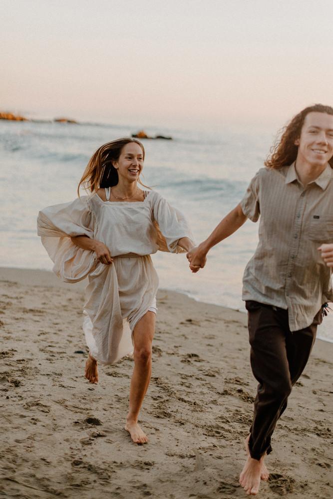 couple running along beach divers cove laguna beach