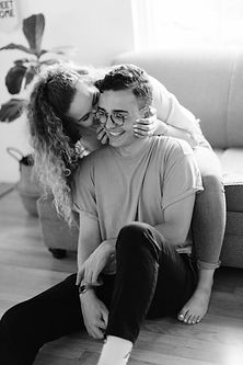 girl kissing guy on cheek home lifestyle session