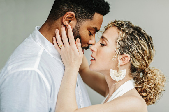 curly haired bride and groom almost kissing