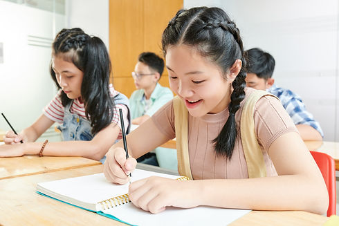 smiling-asian-school-children-writing-textbooks-class.jpg