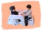 Two little boys sit opposite each other at a table which is painted pale grey to match their chairs. The youngest boy sits in a unique chair with a cushioned headrest and a footrest. The table has a cutout to fit around his chair. The older boy sits on a boxed shaped stool.
