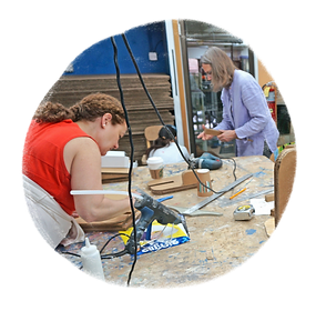 Two women bend over a workbench covered with various tools and materials as they build an adaptation in our workshop.