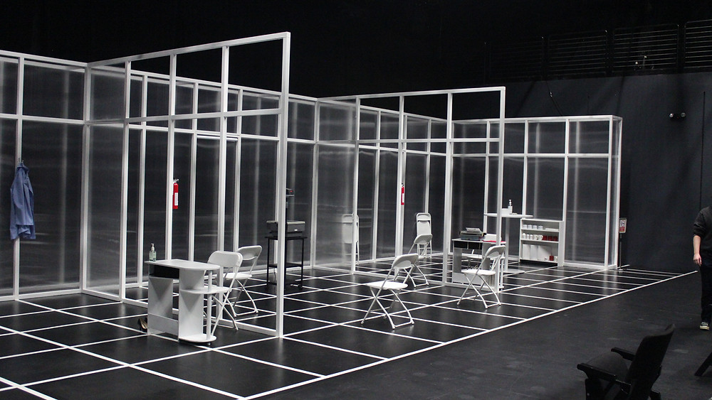 The set on stage is of offices with transparent acrylic sheets for the walls