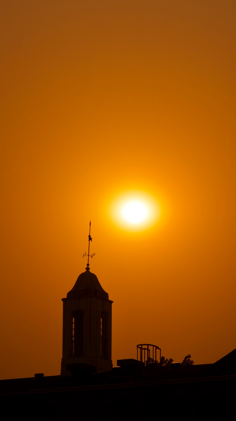 Orange skies due to the nearby fires against Smullin Hall's silhouette