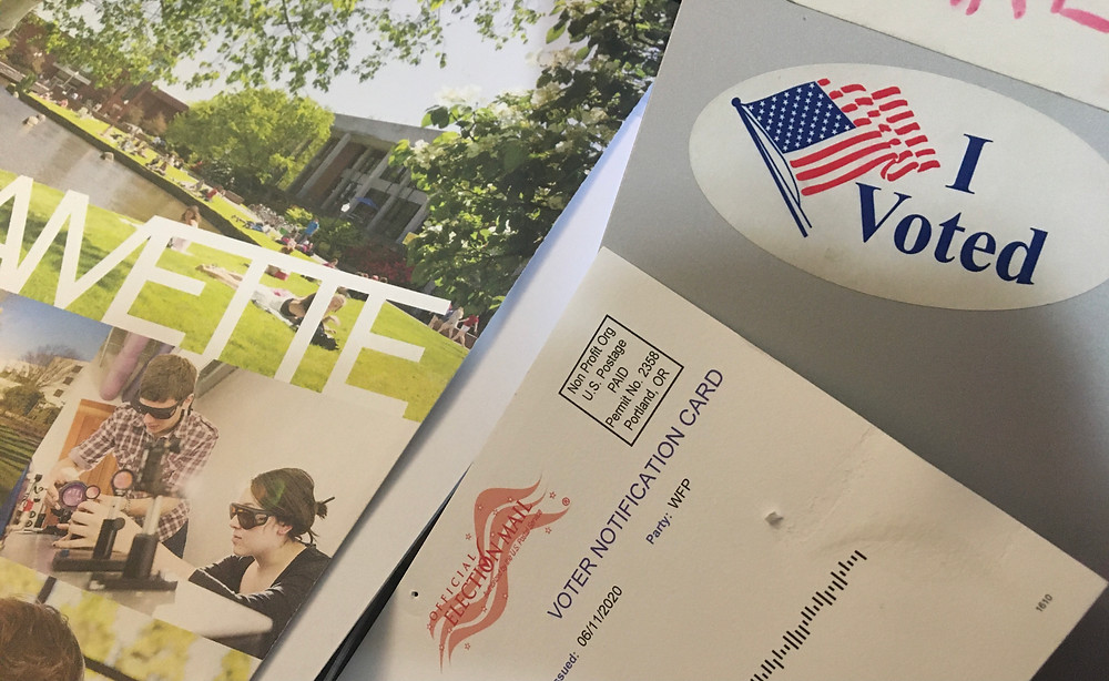 A willamette brochure placed next to an i voted sticker and voter notification card