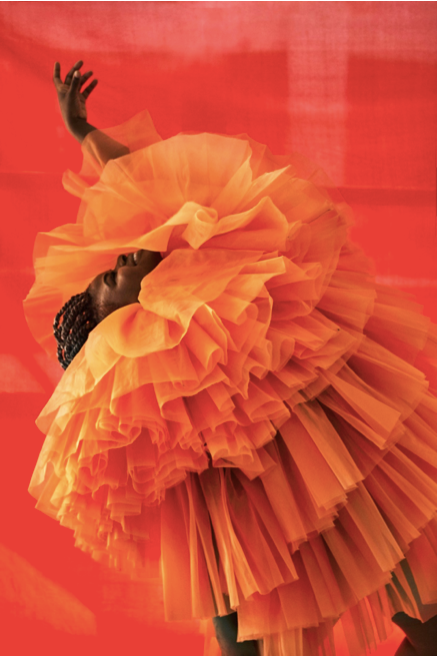 erick hart poses artfully in a orange tulle dress