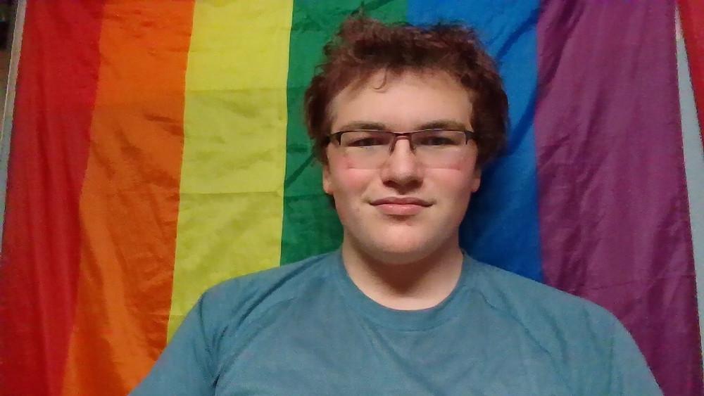 Selfie of Druker against a pride flag