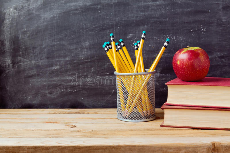 back-to-school-background-books-pencils-apple-over-chalkboard-wooden-table-56035888