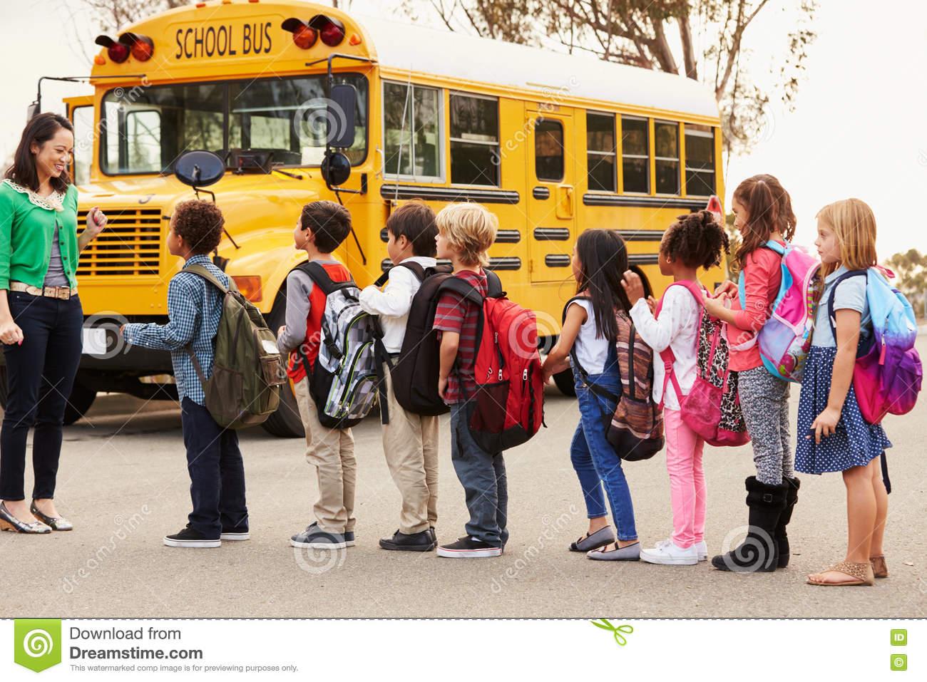 teacher-group-elementary-school-kids-bus-stop-71526884