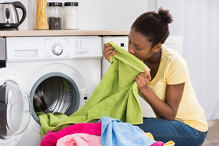 Young African Woman Smelling Clothes Aft