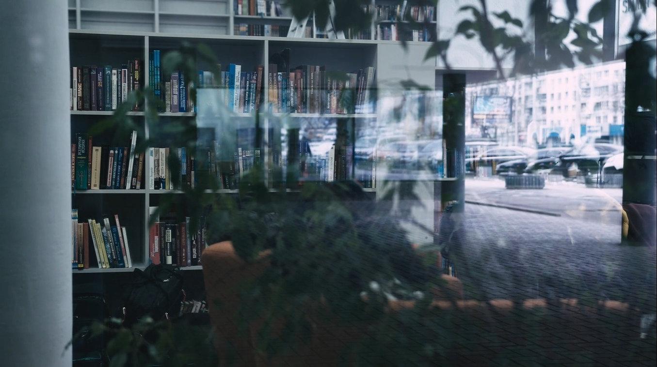 Biblioteca com acesso a rua vista através de vidro.