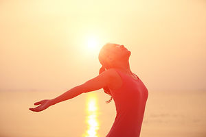 happy woman open arms under the sunrise at sea .jpg