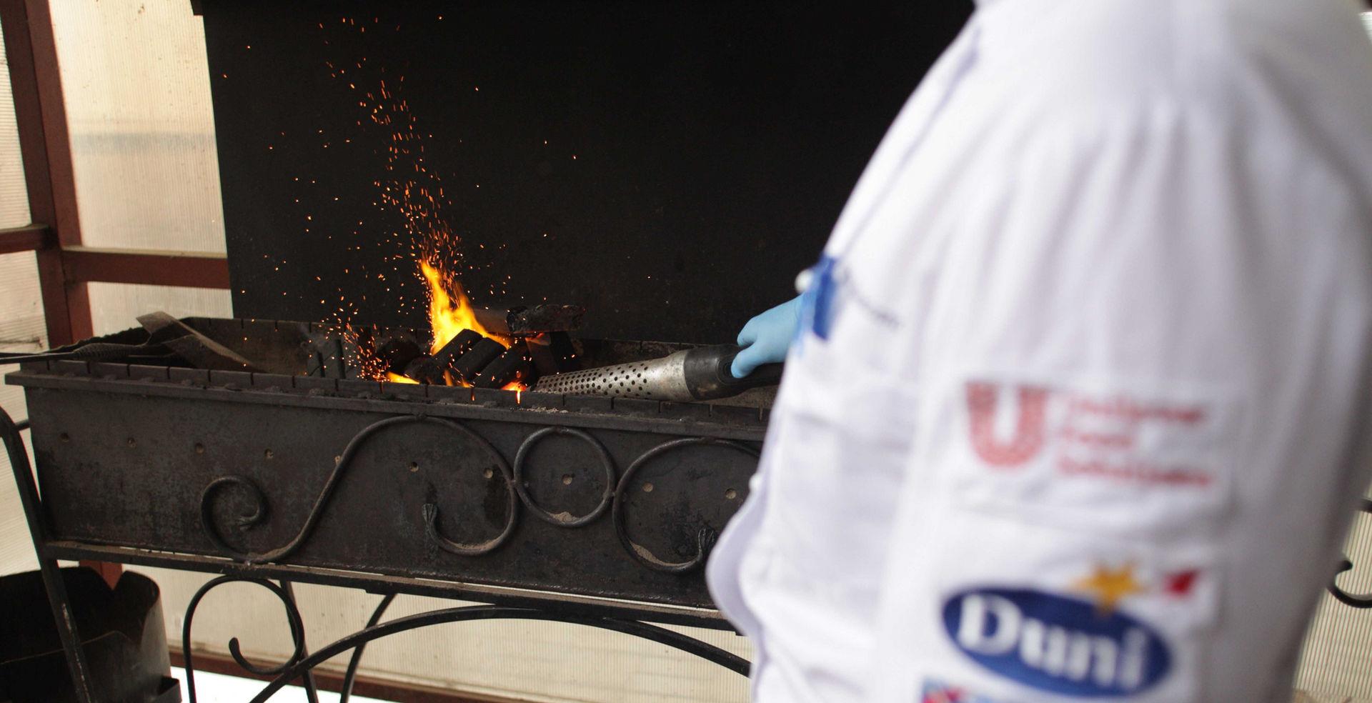 Повар расторана готовит мангал