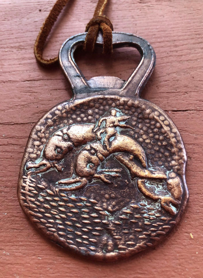 A copper bottle opener with the image of Poseidon riding dolphins. A leather cord attaches at the top.