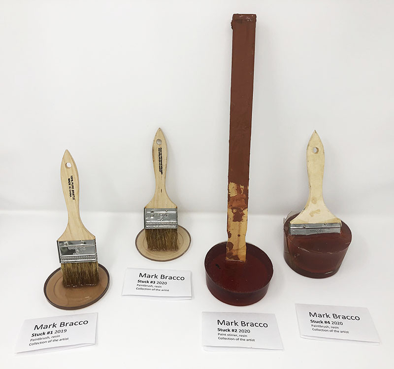 "Accidental art created by Mark Bracco. Photo of paintbrushes and paint stirrer stuck in resin. The placards for the art pieces read ""Mark Bracco/Stuck #1 2019/Paintbrush resin/Collection of the artist""; ""Mark Bracco/Stuck #3 2020/Paintbrush resin/Collection of the artist""; ""Mark Bracco/Stuck #2 2020/Paint stirrer resin/Collection of the artist""; and ""Mark Bracco/Stuck #4 2020/Paintbrush resin/Collection of the artist."""