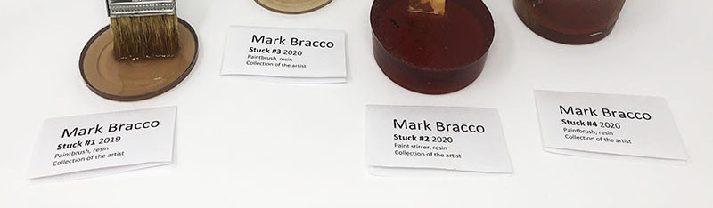 "Close up photo of the placards, that read: ""Mark Bracco/Stuck #1 2019/Paintbrush resin/Collection of the artist""; ""Mark Bracco/Stuck #3 2020/Paintbrush resin/Collection of the artist""; ""Mark Bracco/Stuck #2 2020/Paint stirrer resin/Collection of the artist""; and ""Mark Bracco/Stuck #4 2020/Paintbrush resin/Collection of the artist."""