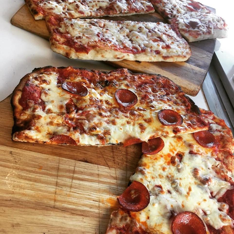 Pepperoni pizza ready to be cut into slices