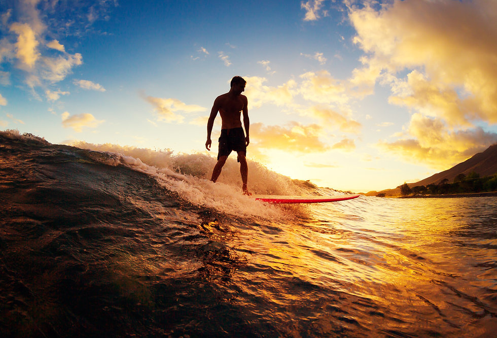 Surfing at Sunset. Young Man Riding Wave