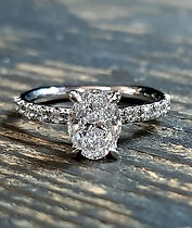 Side stone platinum engagement ring centre oval diamond secured in four cat claws..jpg