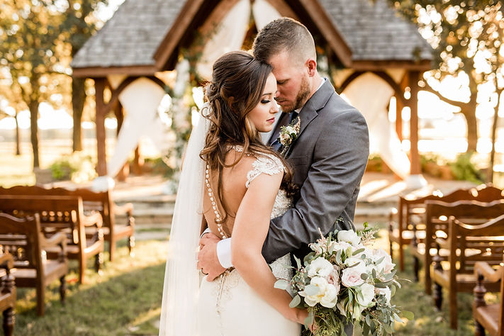 groom embracing bride in front of draped outdoor wedding arch blush bouquet