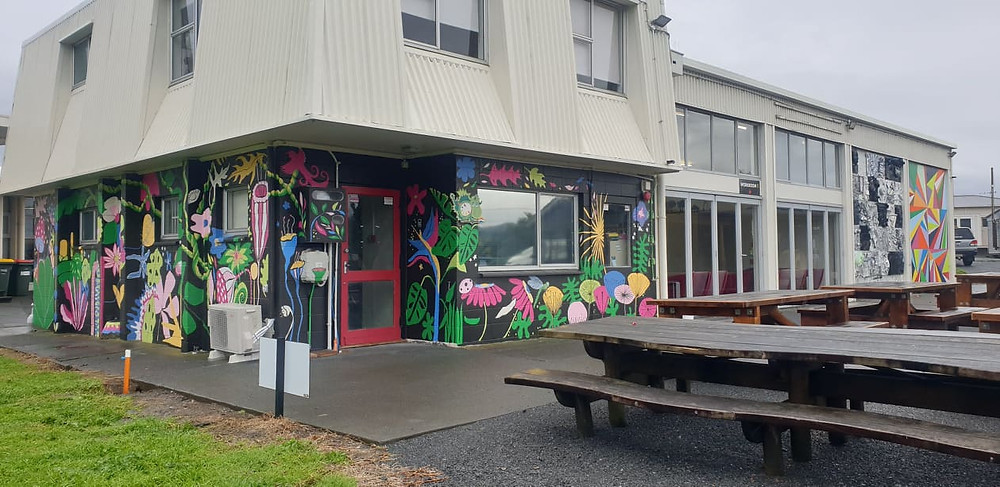 The mural is on the left side and left back corner of the building. The other brightly coloured mural was made by Creative Matters and a group of teens from the area.