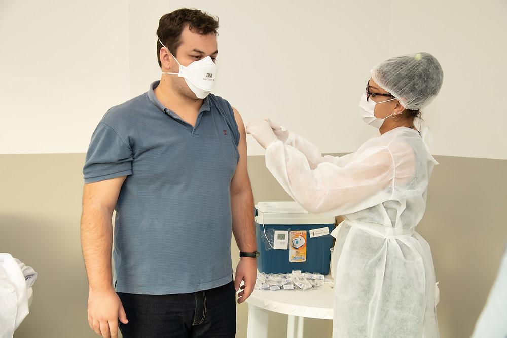 Professor sendo vacinado contra covid-19 na faculdade suprema