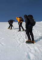 Winter skills course cutting steps with ice axes and crampons