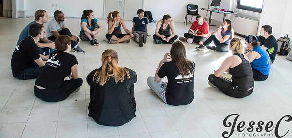 A group of adult students sutting in a circle on the floor having a discussion