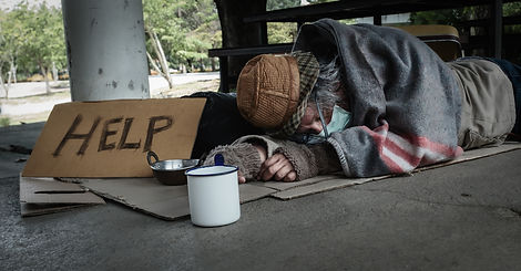 Homeless man lies on the ground while ho