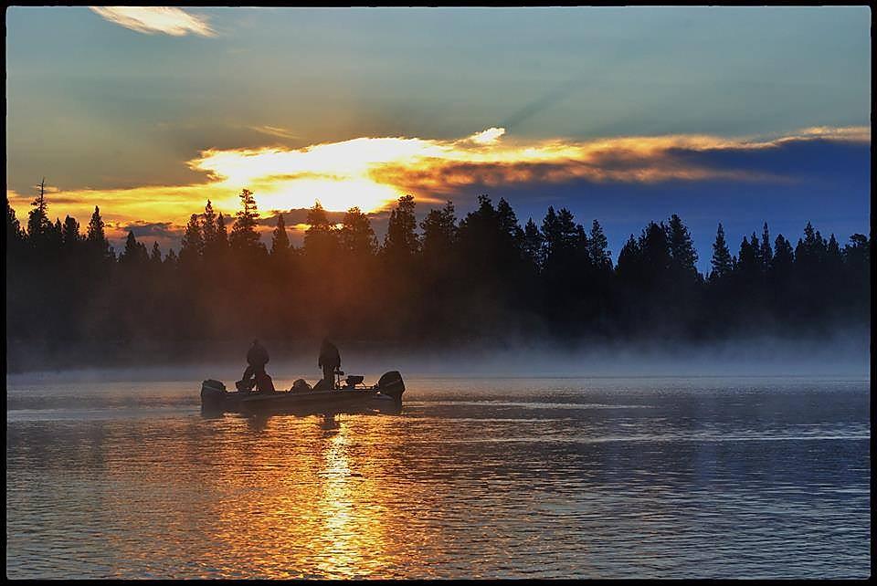 Bass boat fishing on a lake at sunrise