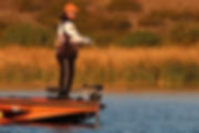man standing on bass boat fishing in lake