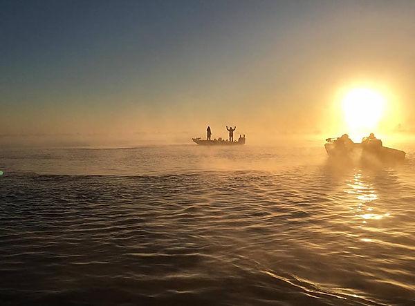 Bass boats oin lake t sunrise