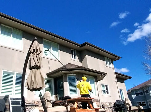 Team member of A Brighter Day Window Cleaning working on a two story home.