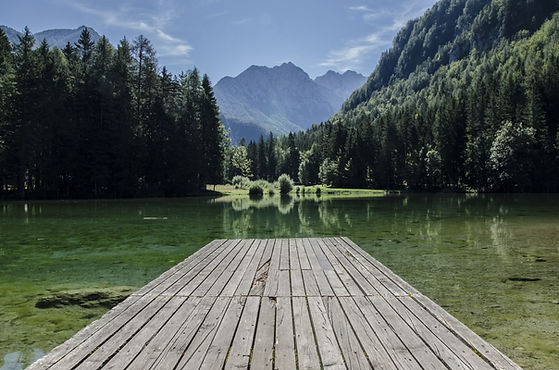 See mit Steg, Berge im Hintergrund