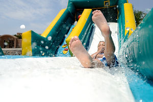 Splash! Young boy sliding down an inflat