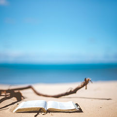 Photo by Ben White on Unsplash of a book on a beach on a sunny day