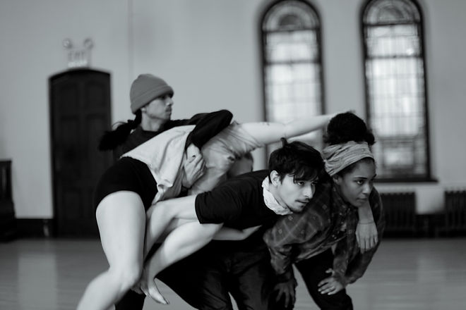 A black and white photo of one two dancers leaning forward with another being lifted by a fourth over a tangle of arms and legs.