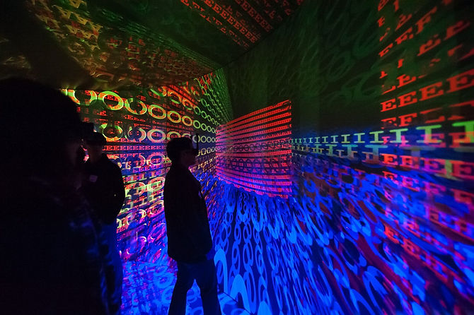 People in sillhouette stand in a room of trippy images of different text in different colors